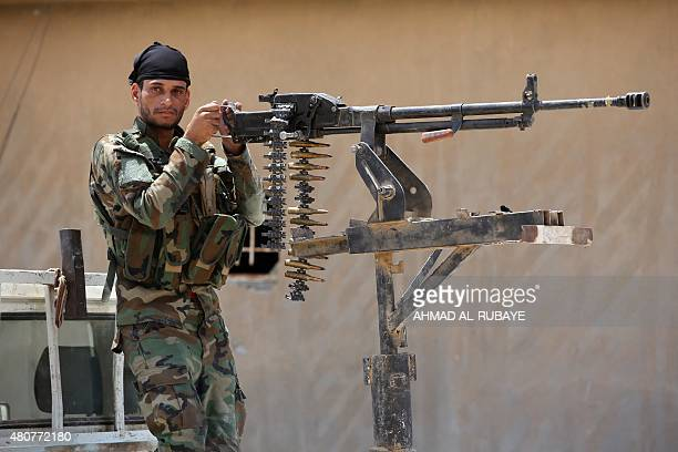 An armed Iraqi Shiite fighter from the Popular Mobilisation units supporting the Iraqi government forces stands next to a heavy machine gun during...