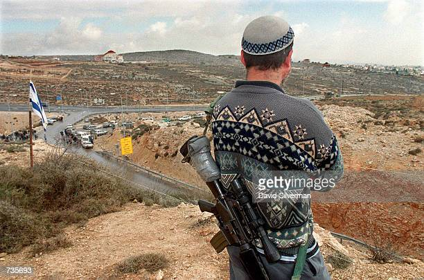 An armed Jewish settler keeps watch over the Ramallah bypass road January 4 a highway which was built to provide settlers with a safe route through...
