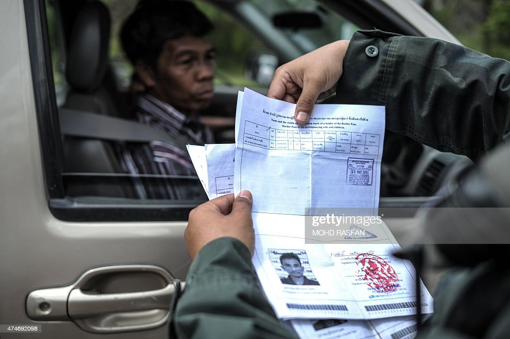An armed Malaysian policeman checks a driver's documentations a day after the government announced the discovery of camps and graves the first such...