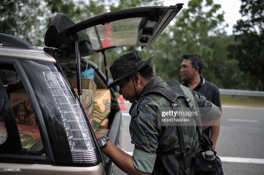 An armed Malaysian policeman inspects a car a day after the government announced the discovery of camps and graves the first such sites found in...