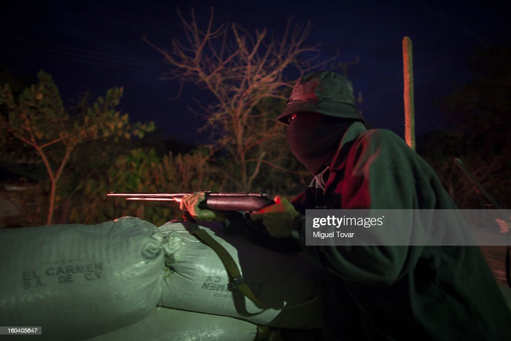 An armed man guards a roadblock at the entrance to the community of Ayutla on January 29, 2013 in Ayutla, Mexico. Hundreds of men have taken up arms in several towns of the southern state of Guerrero to defend their communities against violent criminal gangs.