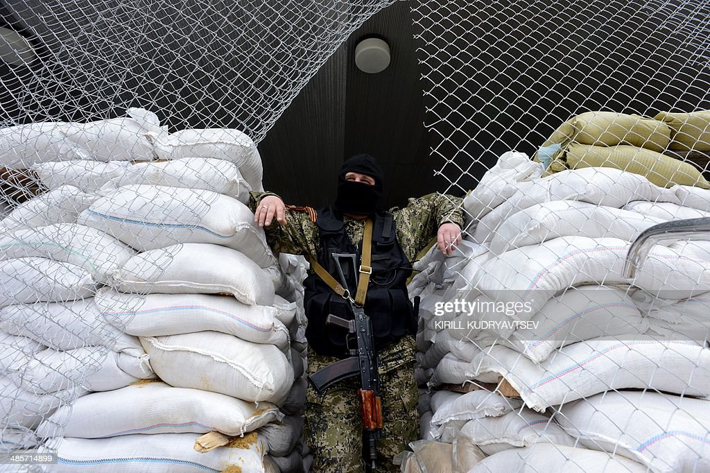 An armed man in military fatigues stands guard at a barricade outside the regional administration building in the eastern Ukrainian city of Slavyansk which is occupied by pro-Russian separatists, on April 20, 2014. Four people were reported killed today in a gun battle in restive eastern Ukraine, shattering a fragile Easter truce in the crisis-hit former Soviet republic. Three pro-Russian militants and one attacker were killed in a deadly firefight at a road block close to the separatist-held town of Slavyansk, local leader Vyacheslav Ponomaryov said.