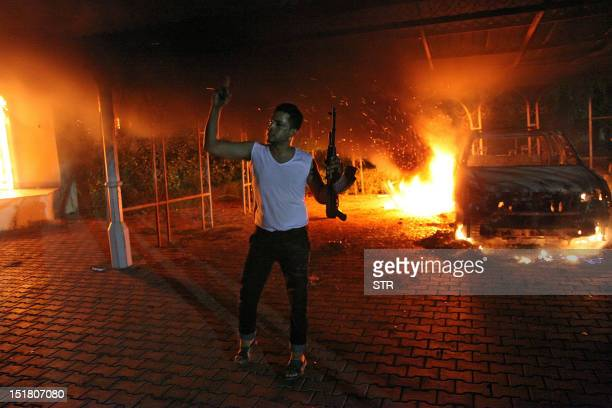 An armed man waves his rifle as buildings and cars are engulfed in flames after being set on fire inside the US consulate compound in Benghazi late...