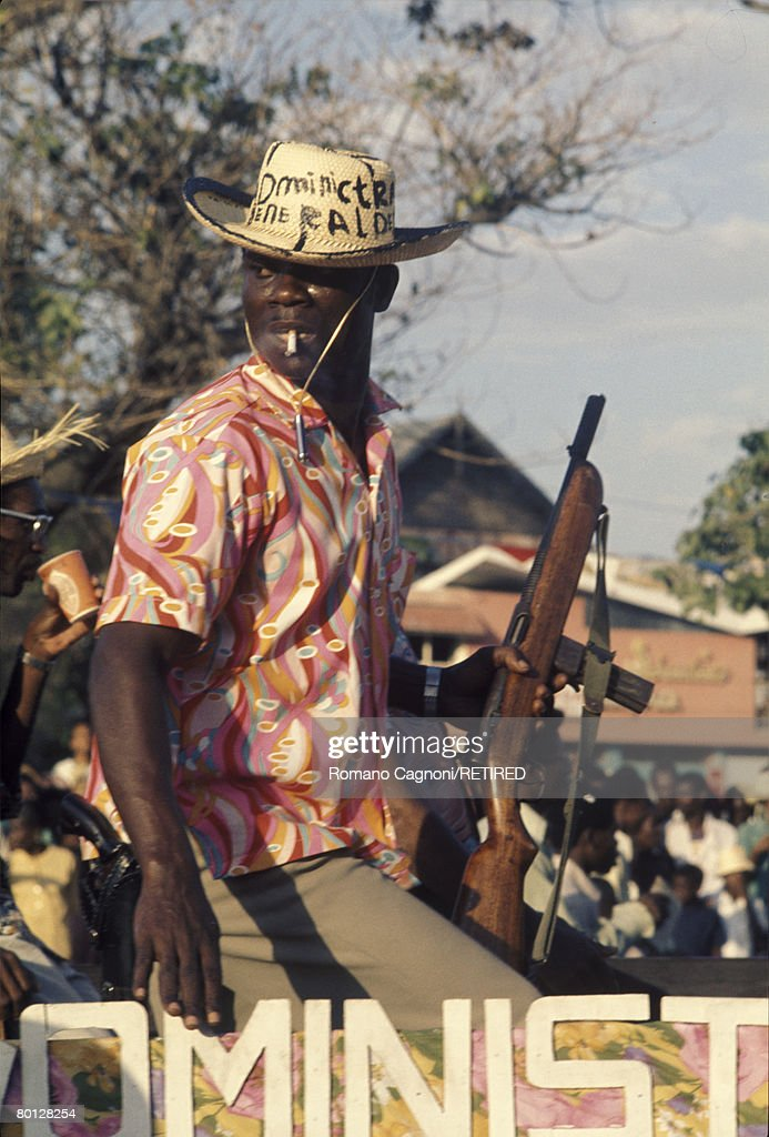 An armed member of the Tonton Macoute (the Haitian militia) controls crowds in the streets of Port-au-Prince, circa 1980.