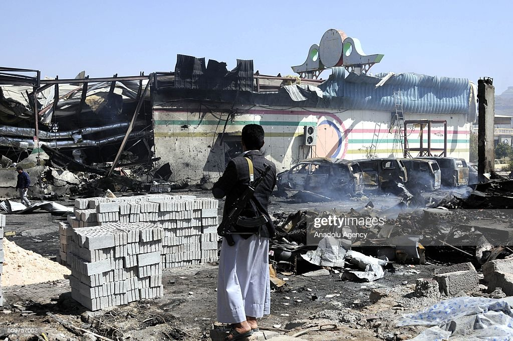 An armed member of Yemeni Ansarullah Houthi movement stands guard near the wreckages of cars and a building after Saudi-led coalition airstrikes hit a bowling saloon at Musbahi district in Sanaa, Yemen on February 12, 2016.