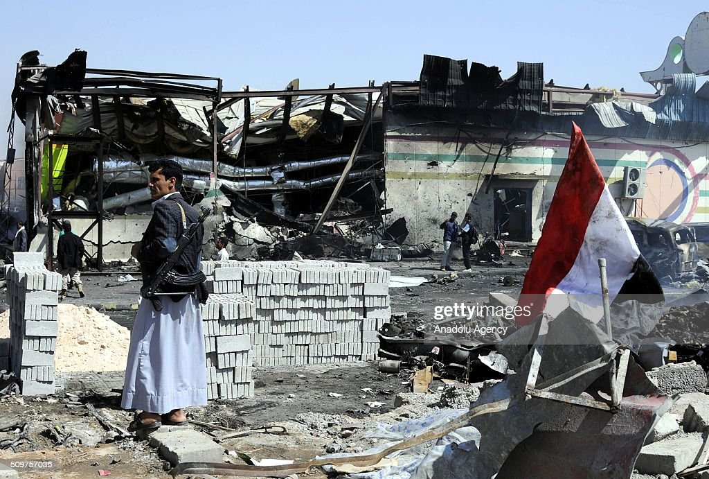 An armed member of Yemeni Ansarullah Houthi movement stands guard around the wreckage of cars and a building after Saudi-led coalition airstrikes hit a bowling saloon at Musbahi district in Sanaa, Yemen on February 12, 2016.