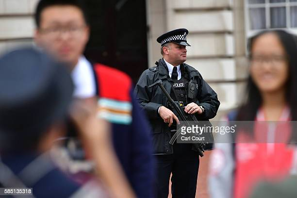 An armed Metropolitan Police officer patrols at Buckingham Palace on August 2 2016 in London England Security measures continue to be high in London...