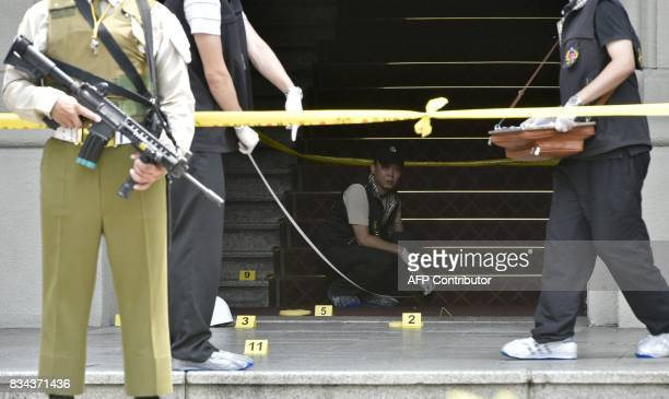 An armed military policeman keeps watch as investigators collect evidence at the scene where a samurai swordwielding attacker slashed a police guard...