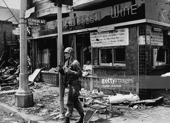 An armed National Guard patrolman leans against a street sign smoking a cigarette and standing in rubble following the Watts riots Los Angeles...