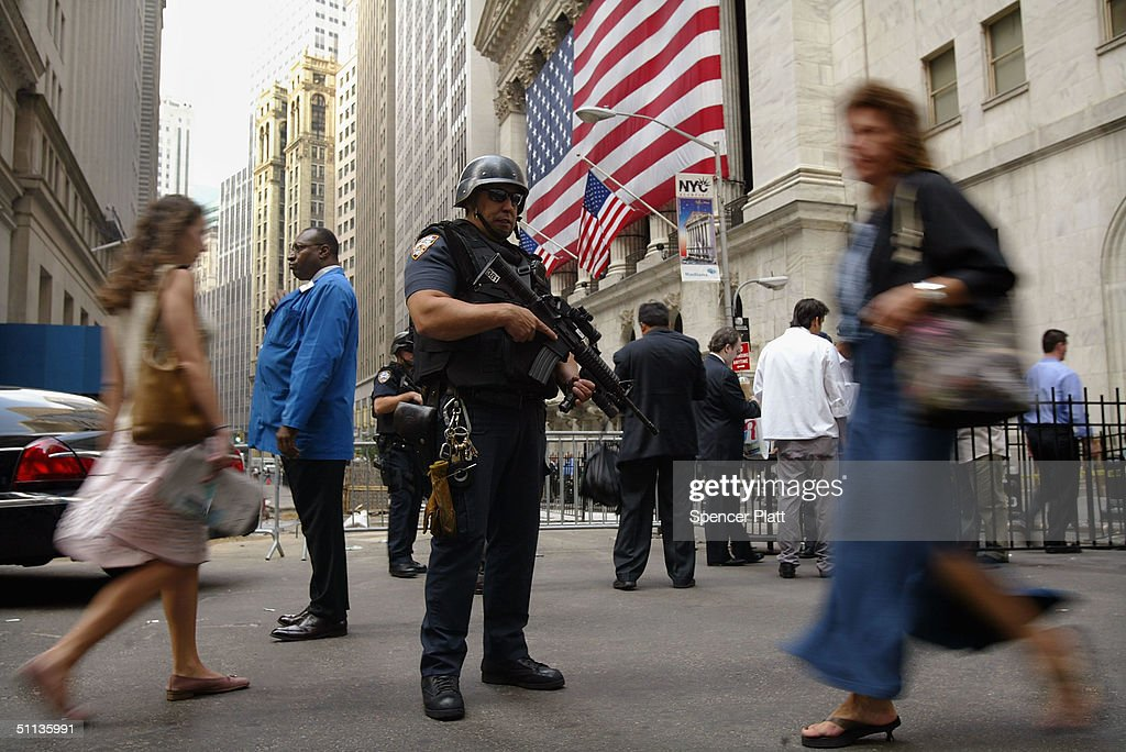 An armed NYPD officer guards the New York Stock Exchange August 2, 2004 in New York City. The U.S. federal government raised the terror alert to orange in New York City, Newark, New Jersey and Washington, DC areas amidst warnings of potential terrorist attacks against financial institutions.