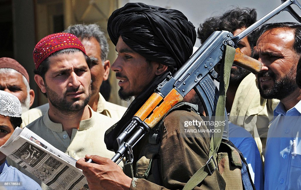 An armed Pakistani Taliban chats with residents in Buner district of the troubled Swat valley on April 23 2009 Pakistan deployed paramilitary troops...