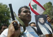 An armed Palestinian Fatah militant holds a picture of Hezbollah Chief Sheikh Hassan Nasrallah during a protest to condemn the Israeli air strike on...