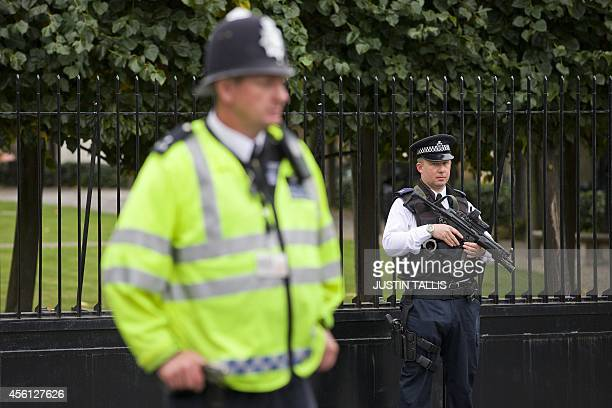 An armed police officer and a police officer stand guard outside the Houses of Parliament where lawmakers are expected to vote in favour of joining...