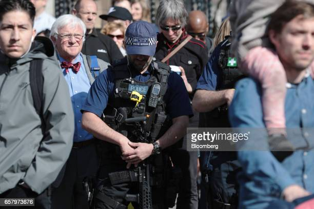 An armed police officer and protesters observe a minute of silence in memory of those who died in the Westminster terror attack during a Unite for...