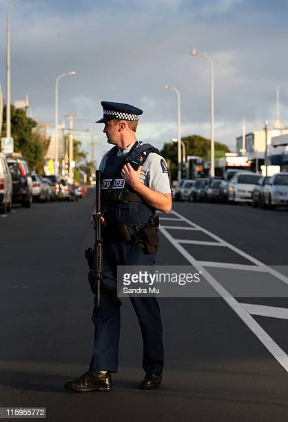 An armed police officer cordons off the main street of Blockhouse Bay on June 13 2011 in Auckland New Zealand The Police are in search of an armed...