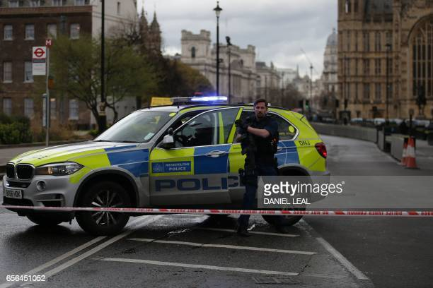 An armed police officer gets out of a car inside a police cordon outside the Houses of Parliament in central London on March 22 2017 during an...
