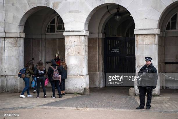 An armed police officer guards Horse Guards on March 24 2017 in London England A fourth person has died after Khalid Masood drove a car into...
