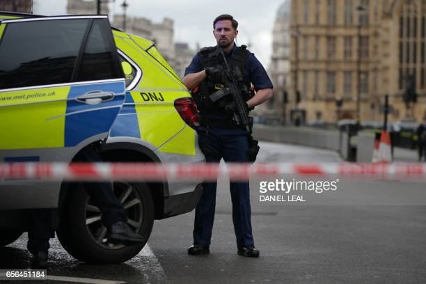 An armed police officer guards inside a police cordon outside the Houses of Parliament in central London on March 22 2017 during an emergency...