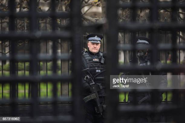 An armed police officer is pictured through the Carriage Gates outside the Houses of Parliament in Westminster on March 24 2017 in London England A...