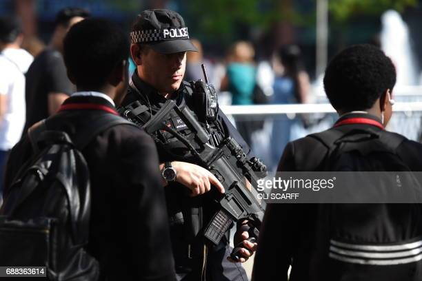 An armed police officer speaks with children on a street in central Manchester northwest England on May 25 2017 three days after the May 22 terror...