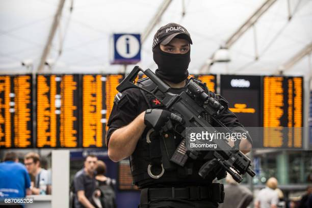 An armed police officer stands at Manchester Piccadilly railway station in Manchester UK on Tuesday May 23 2017 At least 22 people were killed in a...