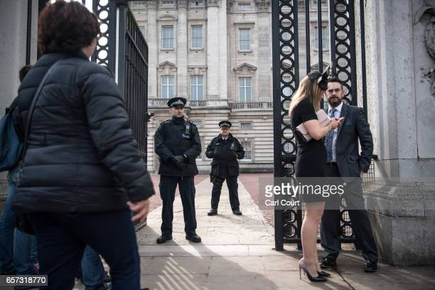 An armed police officer stands behind his unarmed colleague at an entrance to Buckingham Palace on March 24 2017 in London England A fourth person...
