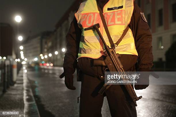 An armed police officer stands guard at a check point in Berlin ahead of the visit of US President Barack Obama on November 16 2016 US President...