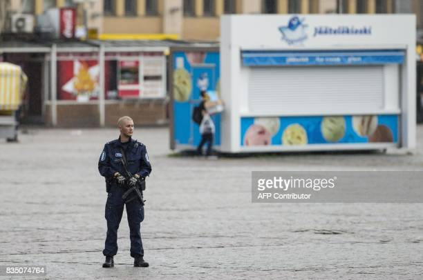 An armed police officer stands guard at the Turku Market Square in the Finnish city of Turku where several people were stabbed on August 18 2017 One...