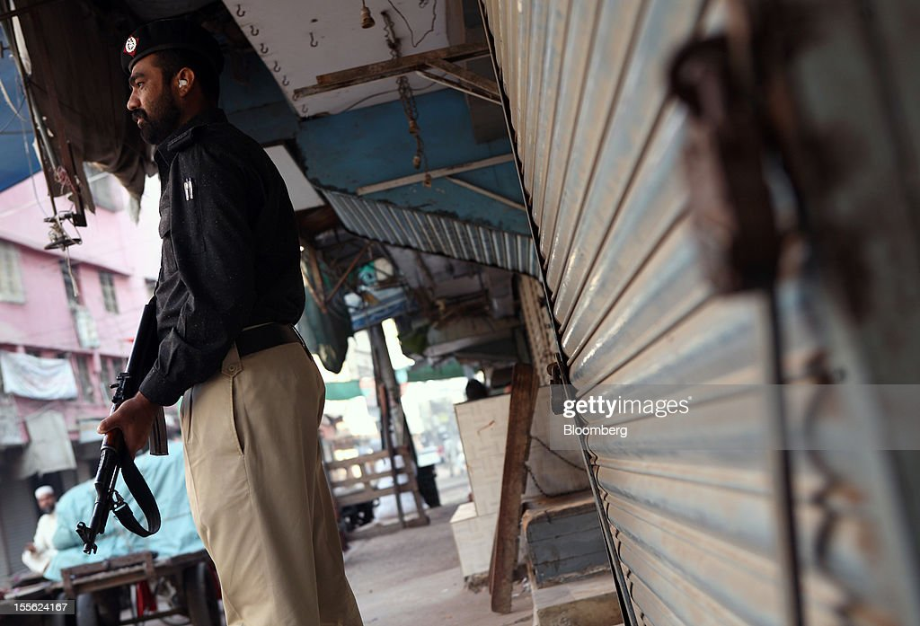 An armed police officer stands guard in front of a locked store in Jodia Bazar in Karachi, Pakistan, on Wednesday, Oct. 31, 2012. Businesses in Pakistan's commercial capital are bracing for a surge in extortion demands as parties representing the city's ethnic communities seek to use their hired guns to build financial war chests ahead of parliamentary polls due in the first half of next year. Photographer: Asim Hafeez/Bloomberg via Getty Images