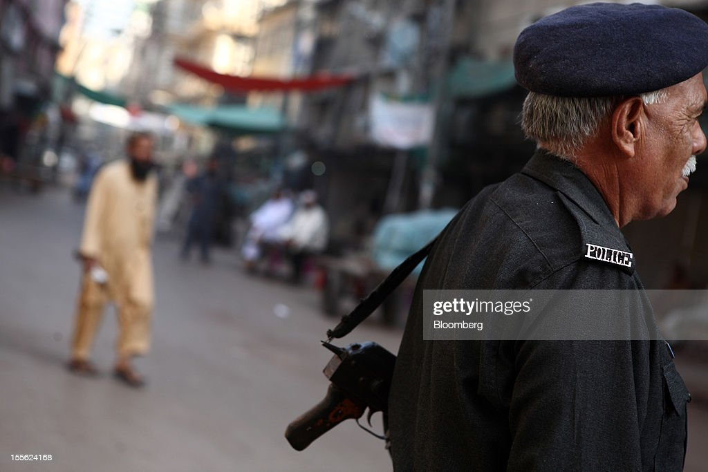 An armed police officer stands guard in Jodia Bazar in Karachi, Pakistan, on Wednesday, Oct. 31, 2012. Businesses in Pakistan's commercial capital are bracing for a surge in extortion demands as parties representing the city's ethnic communities seek to use their hired guns to build financial war chests ahead of parliamentary polls due in the first half of next year. Photographer: Asim Hafeez/Bloomberg via Getty Images