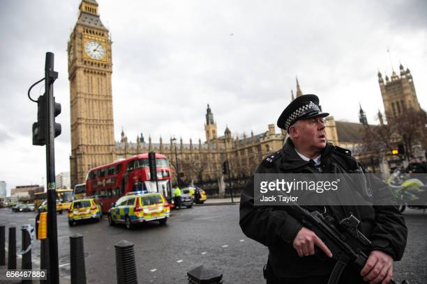 An armed police officer stands guard near Westminster Bridge and the Houses of Parliament on March 22 2017 in London England A police officer has...