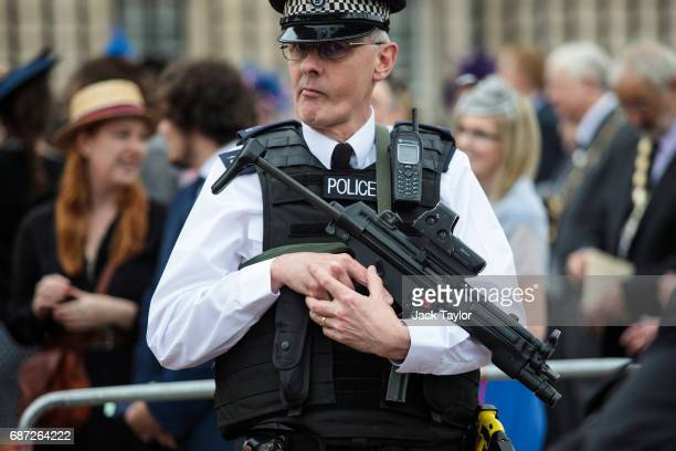 An armed police officer stands guard outside Buckingham Palace on May 23 2017 in London England 22 people including children have been killed and 59...