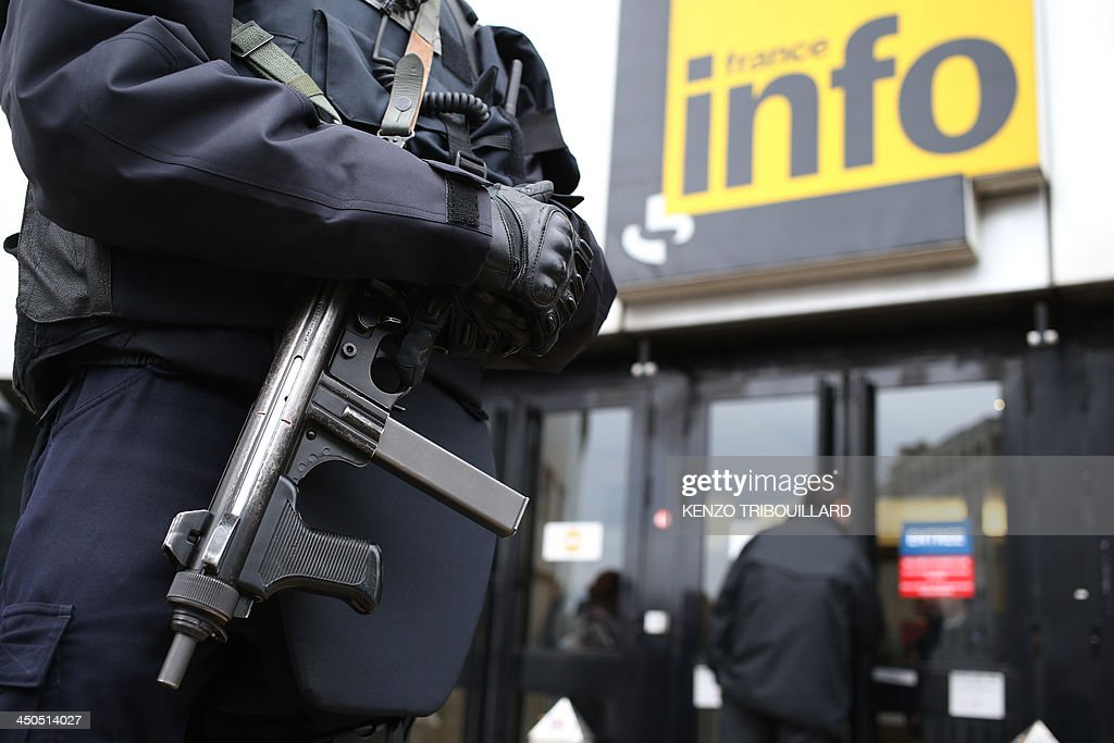 An armed police officer stands guard outside the headquarters of French radio station France Info in Paris on November 19, 2013 as a manhunt is under way in Paris for a lone gunman who shot and critically wounded a newspaper photographer in his office on November 18 before opening fire outside a bank headquarters and hijacking a car. Officers on foot and in squad cars fanned across the nervous city, taking up positions outside media offices, along the Champs-Elysees avenue and at entrances to underground train stations. Investigators have so far been unable to identify the gunman, described by French Interior Minister Manuel Valls as 'a real danger'. AFP PHOTO / KENZO TRIBOUILLARD