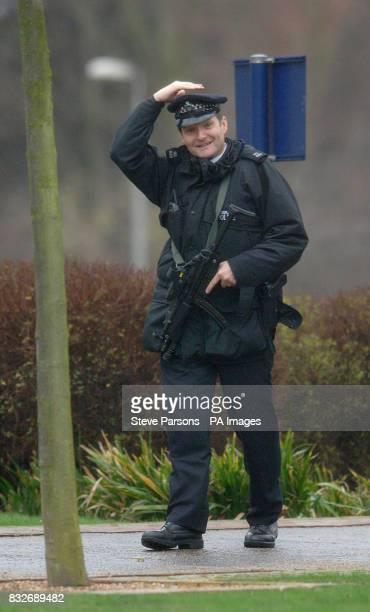 An armed police officer struggles to hold on to his hat in the strong winds at Woolwich Crown Court in south London where six men are accused of...
