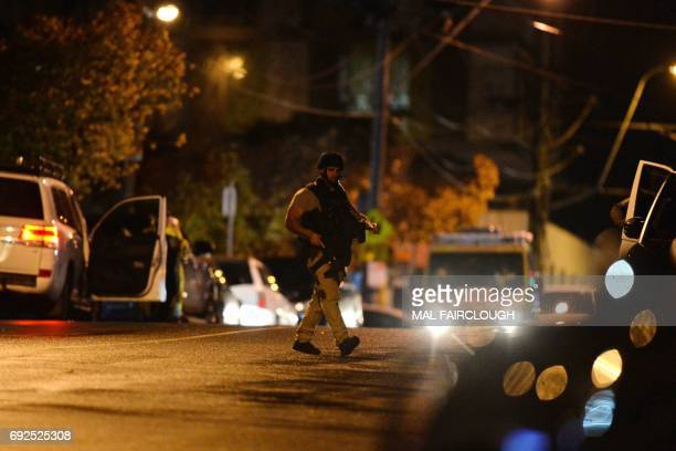 An armed police officer walks at the scene in the Melbourne bayside suburb of Brighton on June 5 after a woman was held against her will in an...