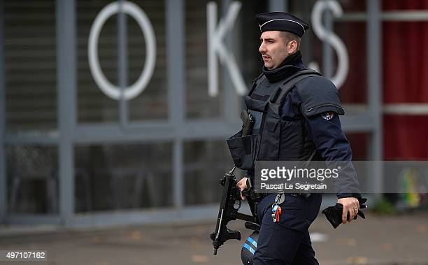 An armed police officer walks near the Bataclan concert hall on November 14 2015 in Paris France At least 120 people have been killed and over 200...