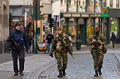 An armed policeman and two soldiers guard the shops on Rue Du Marche Aux Herbes on November 23 2015 in Brussels Belgium Security has been tightened...
