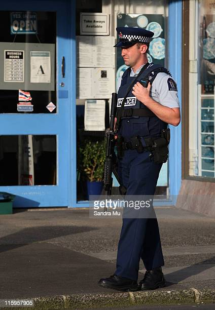 An armed policeman cordons off the main street of Blockhouse Bay on June 13 2011 in Auckland New Zealand The Police are in search of an armed man in...