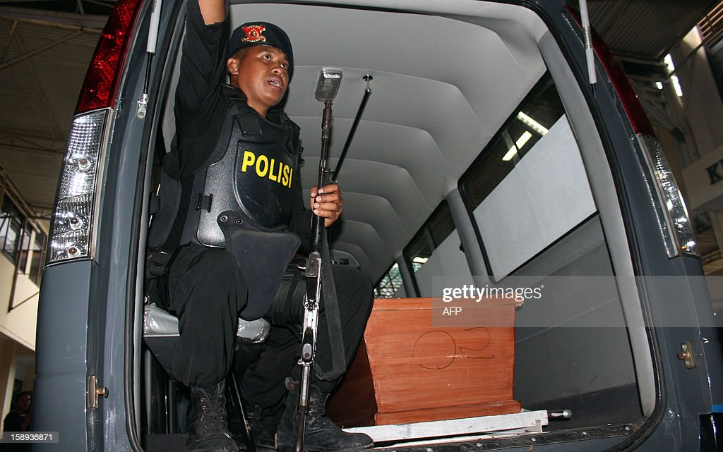 An armed policeman guards the coffin of one of two suspected Islam militants at a police hospital in Makassar, in South Sulawesi, on January 4, 2013 after Indonesia's anti-terror detachment Densus 88 killed them at a university complex. Police said that the men, Samsudin al Aswah alias Abu Uswah, 34, and Kholid al Hasan, 35, were linked to the anti-terror detachment's most wanted man, Santoso, who is still at large. AFP PHOTO / Yudi GUNAWAN
