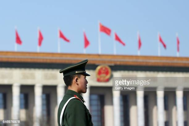 An armed policeman is on alert in front of the Great Hall of the People where fivestar red flags flutter to welcome the upcoming Fifth Session of the...