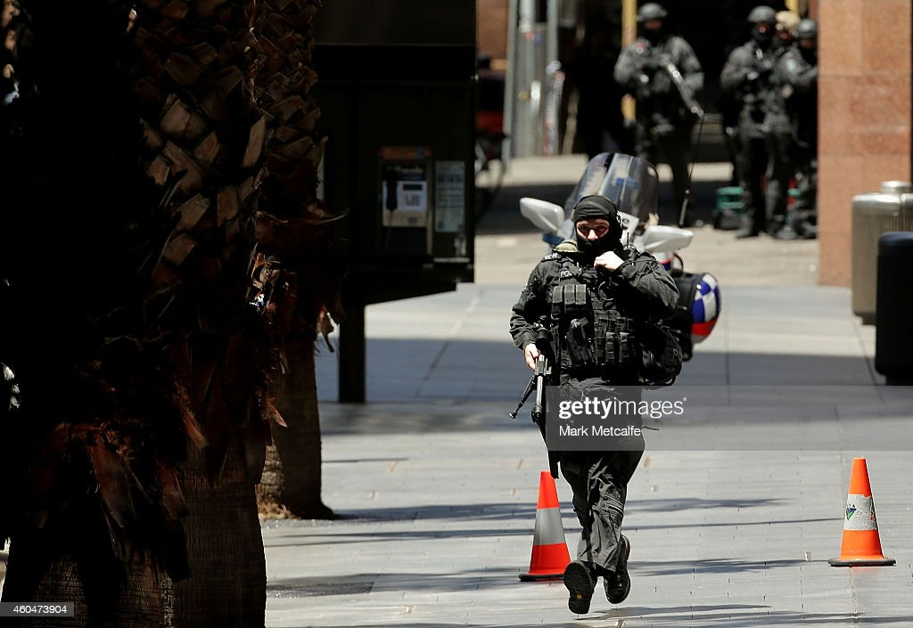 An armed policeman is seen on Philip St running from Martin Place on December 15 2014 in Sydney Australia Police attend a hostage situation at Lindt...