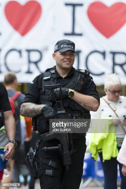 An armed policeman smiles as he stands guard near a message of support at the start of the Great Manchester Run in Manchester on May 28 2017 Britain...