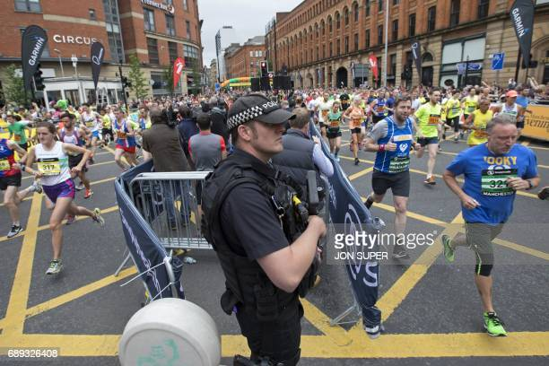 An armed policeman stands guard as competitors including Manchester band New Order's bass player Peter Hook start the Great Manchester Run in...