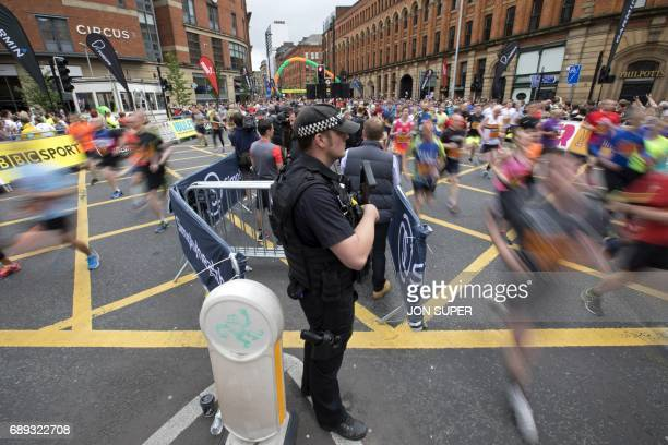 An armed policeman stands guard as competitors start the Great Manchester Run in Manchester north west England on May 28 2017 Britain police have...