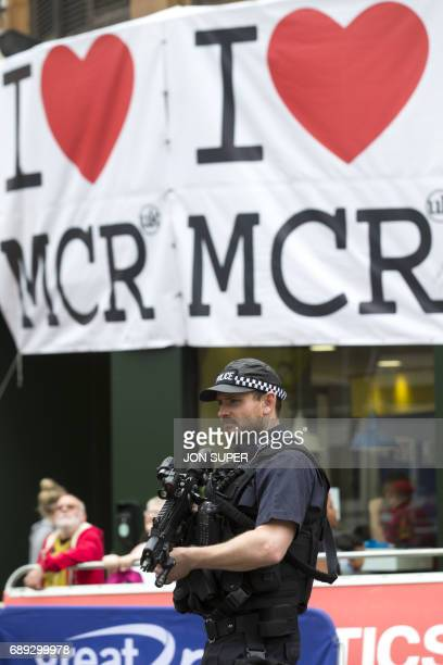 An armed policeman stands guard near a message of support at the start of the Great Manchester Run in Manchester on May 28 2017 Britain police have...