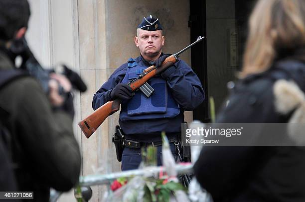 An armed policeman stands guard near the offices of French satirical magazine Charlie Hebdo on January 10 2015 in Paris France Four hostages and...