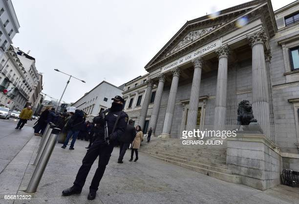 An armed policeman stands guard outside the Spanish Congress 'Las Cortes' after Spanish deputees observed a minute of silence on March 23 in memory...