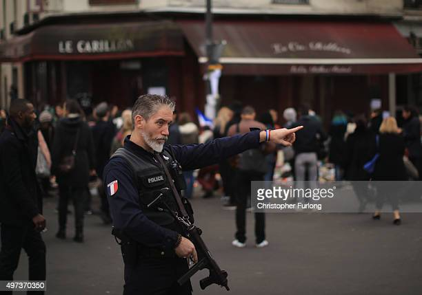 An armed policeman stands outside the Le Carillon restaurant one of the scenes of last friday's terror attacks on November 16 2015 in Paris France...