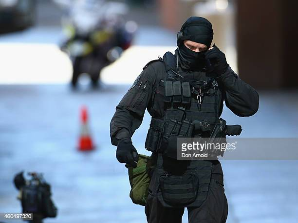 An armed policeman walks northward along Philip St Martin Place on December 15 2014 in Sydney Australia Police attend a hostage situation at Lindt...