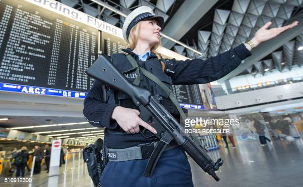 An armed policewoman gestures in Frankfurt Airport on March 22 in Frankfurt western Germany The increased security comes in the wake of the...